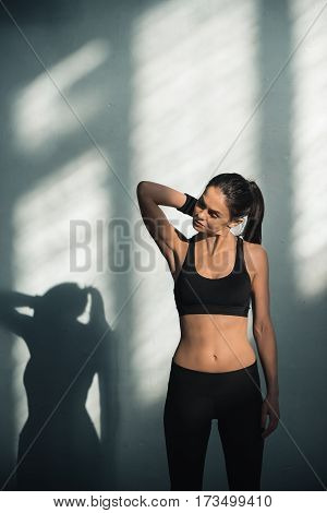 portrait of sporty woman with shadows stretching