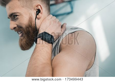 portrait of smiling sporty man with smartwatch on wrist