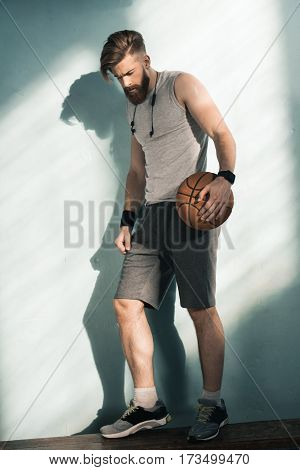 side vie wof pensive sporty man holding basketball ball in hands