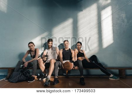 serious sporty men and women sitting on bench in gym