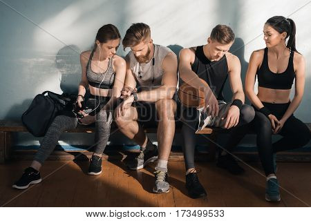sporty men and women sitting on bench after training in gym