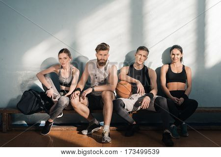 tired sporty men and women sitting on bench in gym