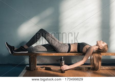 tired sporty woman lying on bench with sports bottle