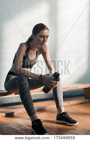 concentrated sporty woman sitting on bench with bottle of water