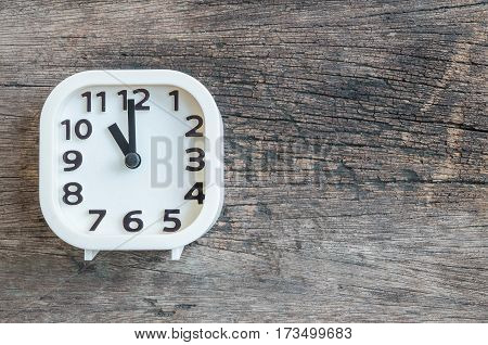 Closeup white clock for decorate in 11 o'clock on old wood floor textured background with copy space