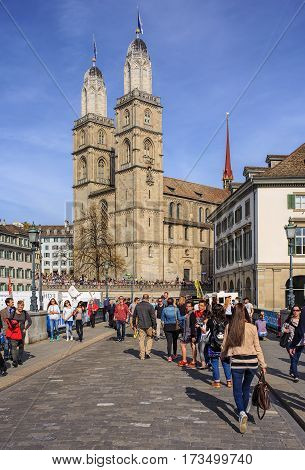 Zurich, Switzerland - 13 April, 2015: people on Munsterbrucke bridge, towers of the Grossmunster Cathedral decorated with flags of Zurich in the background. Zurich is the largest city in Switzerland and the capital of the Swiss canton of Zurich.