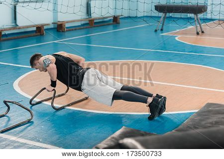 Young sportsman doing gymnastic exercise on hands in sports hall