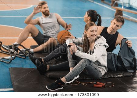 Smiling young sporty people sitting on mats and talking in sports hall