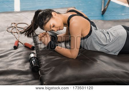 Young sporty woman with closed eyes exercising on mat in sports hall