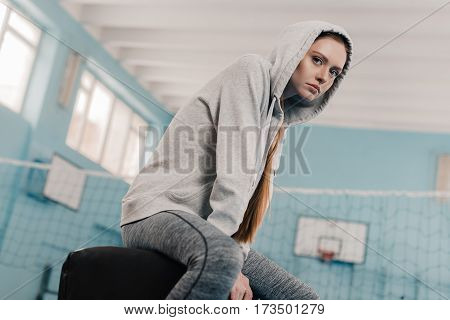 Young athletic woman in sportswear sitting on pommel horse in sports hall