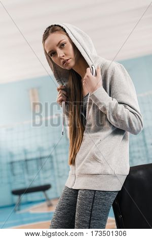 Young sporty woman leaning at pommel horse in sports center