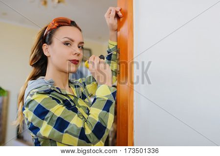 A Young Woman Builder Working Using A Screwdriver