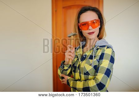 Woman With Hammer And Orange Protective Glasses