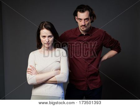 Young couple  against gray background, they are looking displeased and bewildered