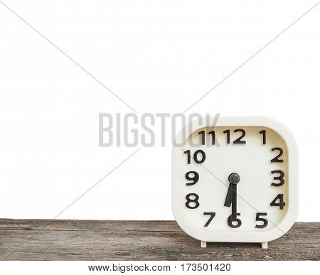 Closeup white clock for decorate show half past six or 6:30 a.m. on old brown wood desk isolated on white background with copy space
