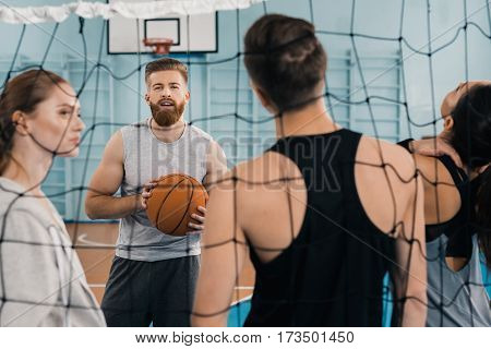 Bearded young sportsman with ball talking with teammates in sports hall