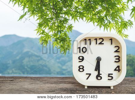 Closeup white clock for decorate show half past six or 6:30 a.m. on blurred mountain view background