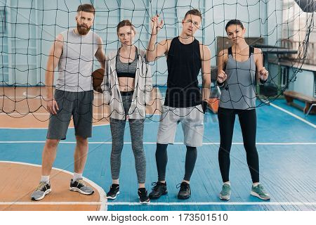Young sportsmen and sportswomen looking through net in sports center
