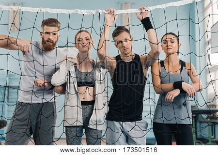 Sporty young people looking at camera through net in sports hall