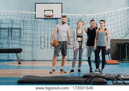 Sporty young people standing with ball and looking at camera in gym