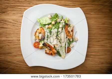 Caesar Salad with shrimps served on a plate in restaurant