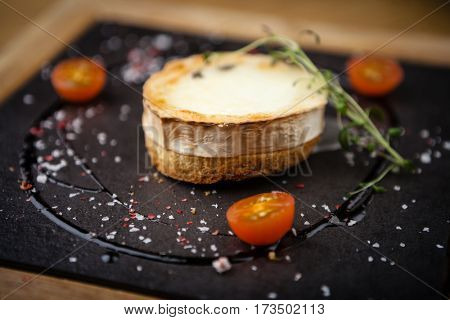 Toast with soft goat cheese served with cherry tomatoes on a stone board