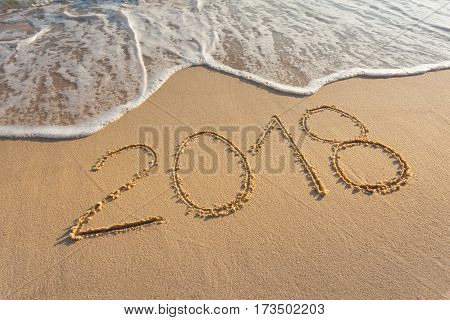 Number 2018 handwritten on sandy coastline. Concept of upcoming new year and passing of time.
