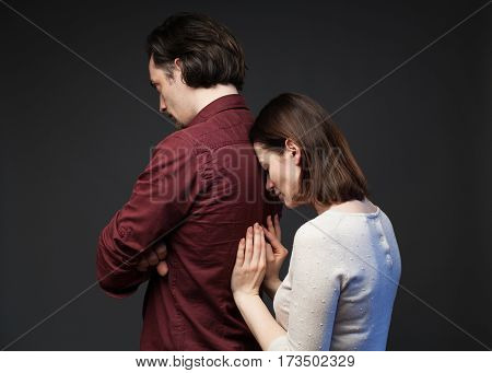 Misunderstanding in the family - the man is standing turned away with crossed hands, the woman is touching his back tenderly, gray background