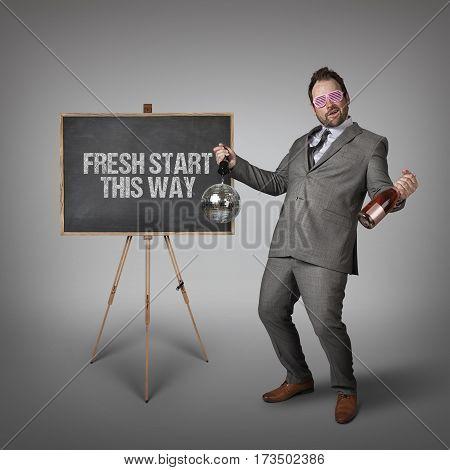 Fresh start this way text on  blackboard with drunk businessman