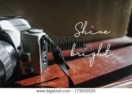 Isolated calligraphy on Camera film on brown wooden stairs. Quote about photo and photography. Shine bright.