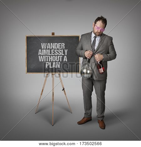 Wander aimlessly without a plan text on blackboard with businessman and key