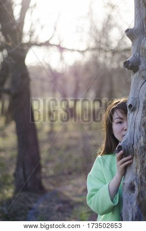 beautiful young woman hiding behind a tree in the forest