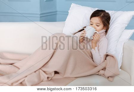 Stay warm. Pleasant sick little girl suffering from flu and drinking tea while lying in her bad