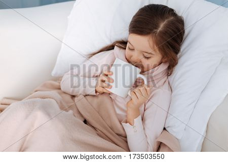 I will recover. Pleaant little girl lying in bed and drinking tea while suffering from flu