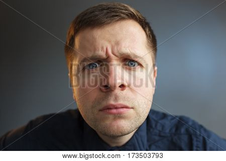 young man looking seriously forward, carefully looking
