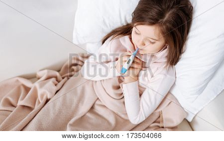Help me to recover. Pleasant ill little girl lying in bed and measuring temperature while resting at home