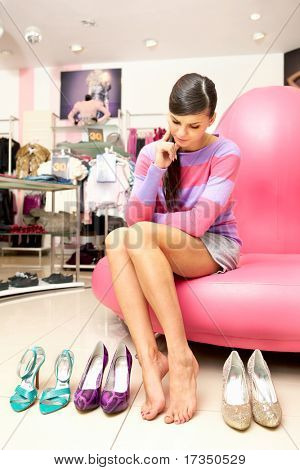 A young women sitting in shop and thinking what shoes to buy