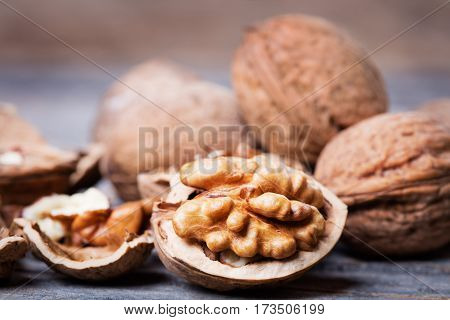 heap of walnuts with nutshell on wooden background