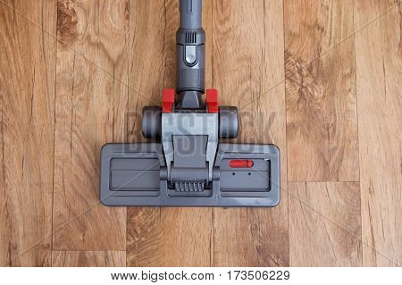 One person hoovering a parquet wooden floor
