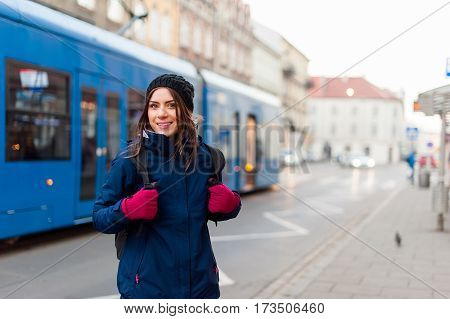 Girl with backpack smiling in the tram station on the background while visiting the city and having a good time.