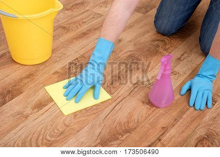 A hand cleaning one wooden parquet floor