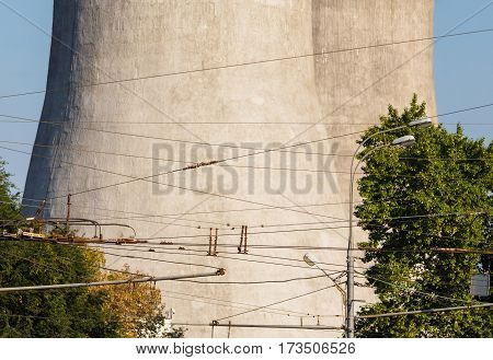 Close up of cooling tower with trees and trolley wires
