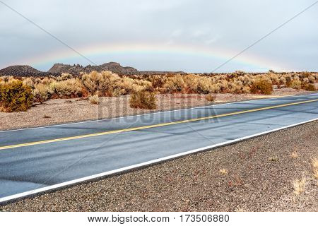 Open highway and rainbow in California, USA.
