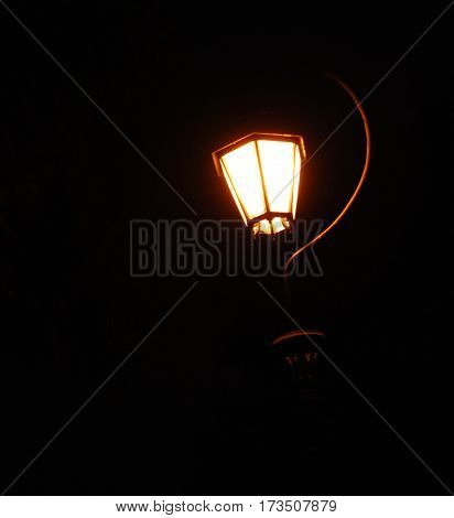 bright lit lantern suspended with black background
