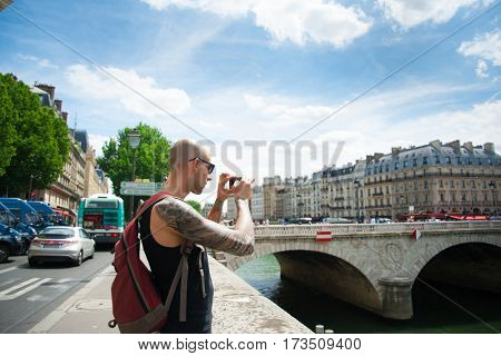 Man making a photo of a city using phone.  Male tourist taking pictures on smart phone from bridge on holidays