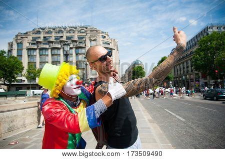 Cheerful yong man taking a selfie photo with a street clown outdoors
