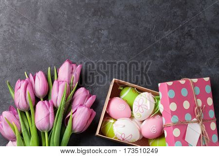 Fresh pink tulip flowers and easter eggs in gift box on stone table. Top view with copy space