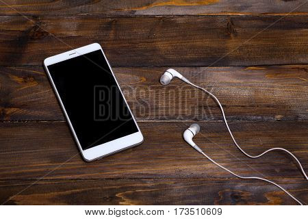 White Mobile Phone On Wooden Wooden Background With Headphones