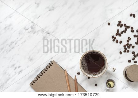 Morning composition with a cup of black coffee and a notebook on a marble surface with space for text top view