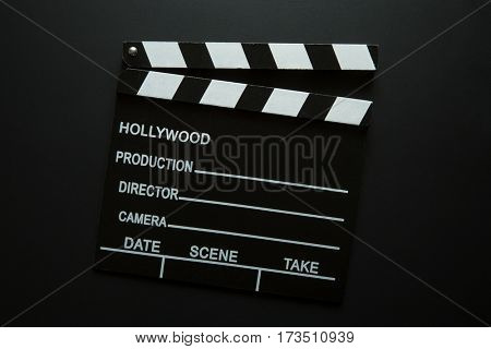 The vintage clapperboard on black background. Top view.